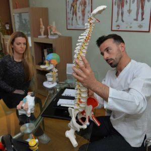 osteopata illustra spina dorsale a paziente